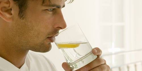 Мужчина пьет воду с лимоном