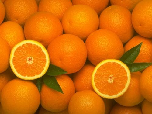 Много апельсинов неочищенных и разрезанных