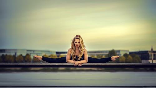 Девушка сидит в продольном шпагате
