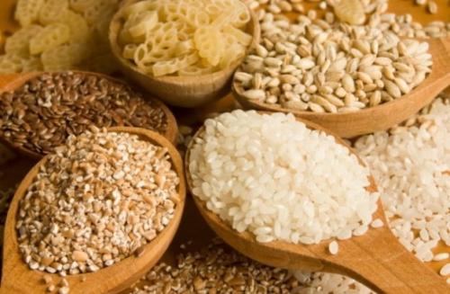 Коричневый и белый рис в деревянных ложках