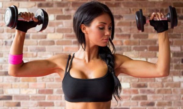 Девушка делает упражнения с гантелями на руки